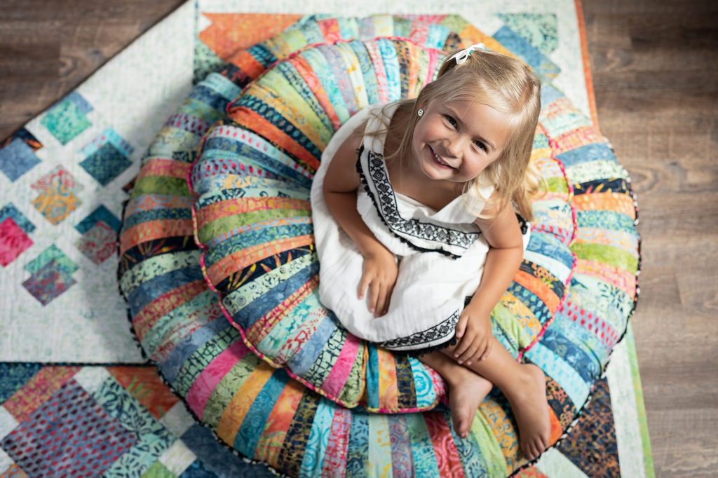 Smiling girl on batik pillows and cushions authentic I luv luci collection